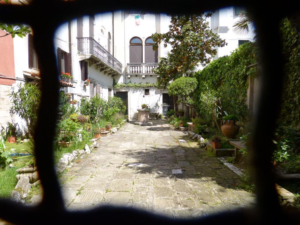 Der Blick durch ein Tor in einen blühenden Hinterhof