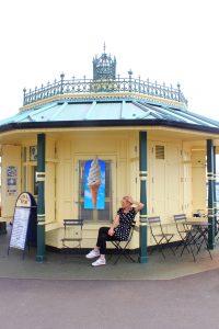 Katharina sitzt auf einem Stuhl vor einem Pavillon in Brighton