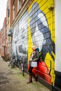 Nachdenklich vor einem gelben Graffiti in Rotterdam